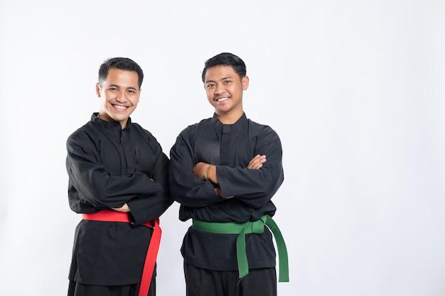 プンチャックシラットのユニフォームを着た2人のアジア人男性が交差した手で立っています