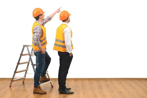 Двое строителей возле жеста лестницы на фоне белой стены