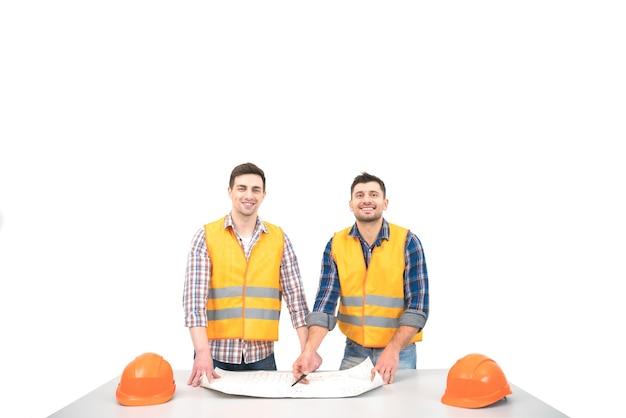 Два строителя с бумагой на столе стоят на белом фоне