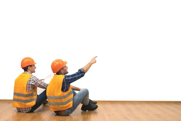 Два строителя с бумагой сидят на полу на фоне белой стены.
