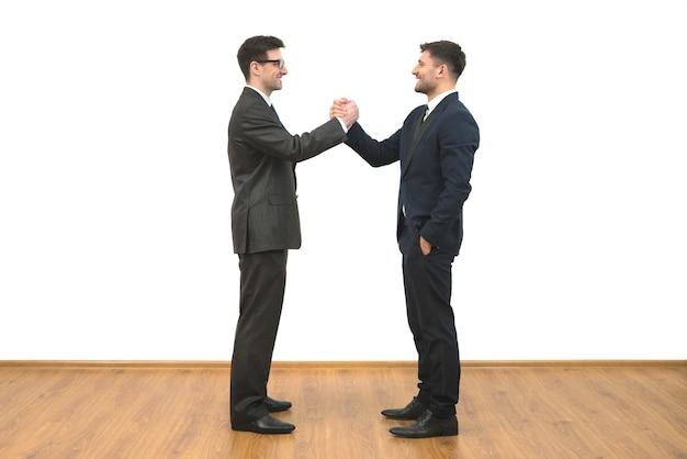 흰 벽 배경에 인사하는 두 사업가