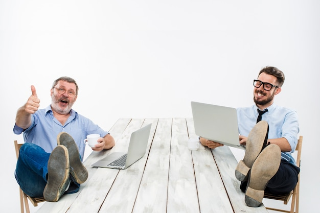 ラップトップに取り組んでいるテーブルの上の足を持つ2人のビジネスマン