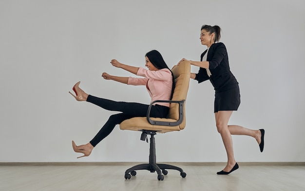 Две бизнес-леди играют со стулом