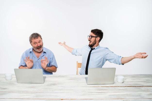 白い背景の上のオフィスで一緒に働いている2人の同僚。どちらもコンピューターの画面を見ています。どちらも驚いた。前向きな感情と朗報の概念