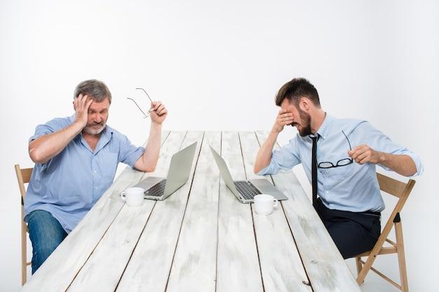 白い背景の上のオフィスで一緒に働いている2人の同僚。どちらもコンピューターの画面を見ています。どちらも非常に動揺しています。否定的な感情と悪いニュースの概念