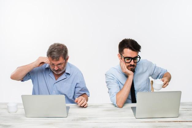 白い背景の上のオフィスで一緒に働いている2人の同僚。どちらもコンピューターの画面を見ています。否定的な感情と悪いニュースの概念