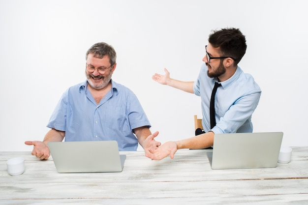 白い背景の上のオフィスで一緒に働いている2人の同僚。幸せな男性は両方とも良い知らせを受け取っています。ビジネスでの成功のコンセプト。