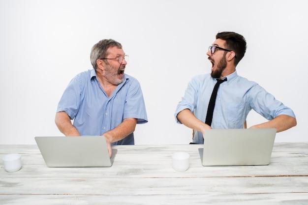 Двое коллег, работающих вместе в офисе на белом фоне. оба счастливых мужчины получают хорошие новости. концепция успеха в бизнесе.