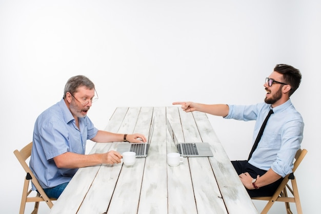 Двое коллег, работающих вместе в офисе на белом фоне. один мужчина смотрит в экраны компьютеров. другой мужчина смеется над другим