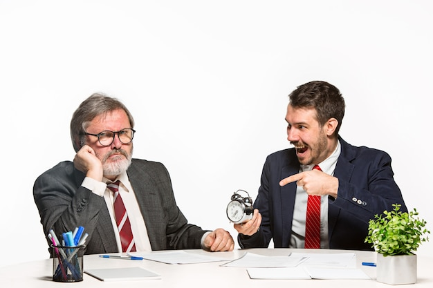 Двое коллег, работающих вместе в офисе на белом фоне. они активно и эмоционально обсуждают текущие планы с часами.