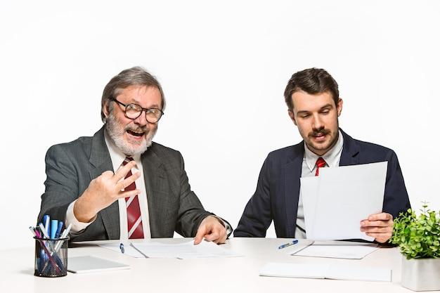 白い背景の上のオフィスで一緒に働いている2人の同僚。彼らは積極的かつ感情的に現在の計画を話し合っています
