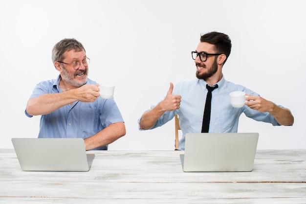 Двое коллег, работающих вместе в офисе на белом фоне