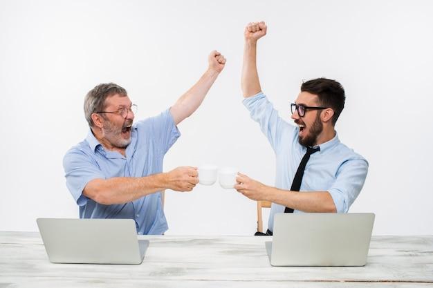 Два коллеги, работающие вместе в офисе на белом фоне