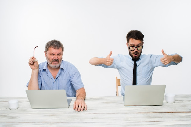 白い壁のオフィスで一緒に働いている2人の同僚