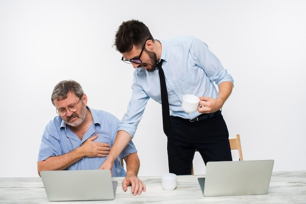 Два коллеги, работающие вместе в офисе на белой стене