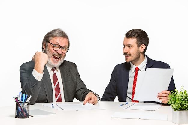 Двое коллег, работающих вместе в офисе на белом.