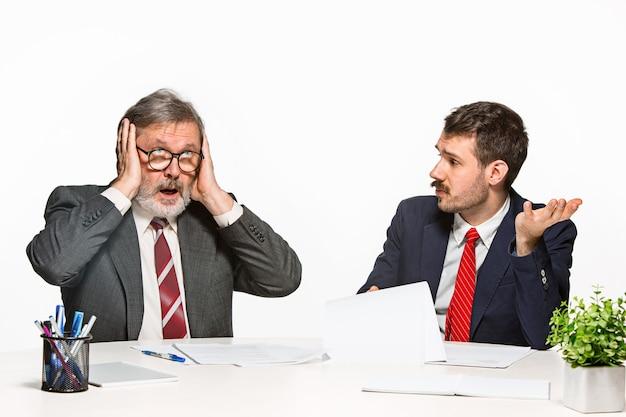 白のオフィスで一緒に働いている2人の同僚。