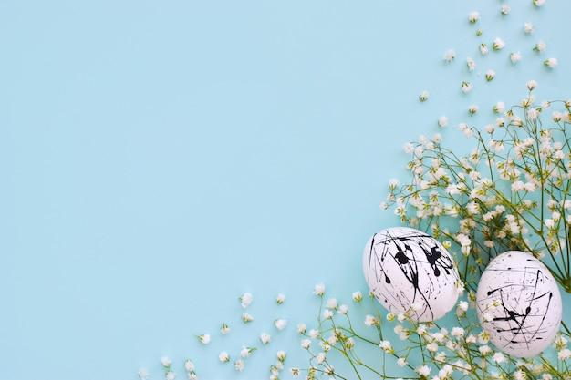 2つの卵は白い色で、青い背景に黒い斑点と花があり、スペースのコピーがあります。イースター。ミニマリズム。お祭りの背景。はがき。フレーム