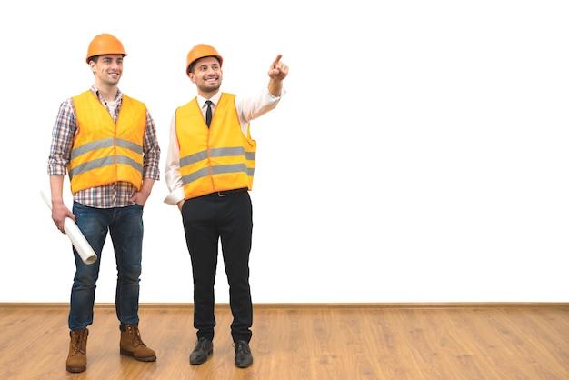 Два инженера жестикулируют на фоне белой стены