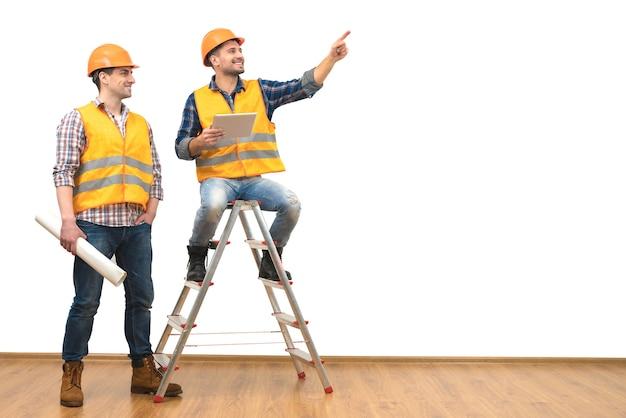 Два инженера возле лестницы жест на белом фоне стены