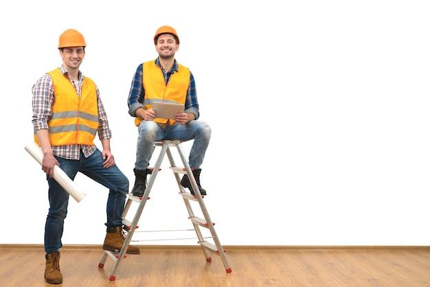 Два инженера возле лестницы на фоне белой стены