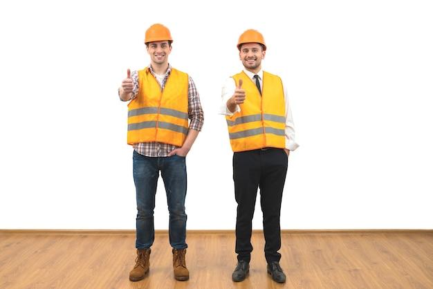 Два инженера поднимают палец вверх на белом фоне стены