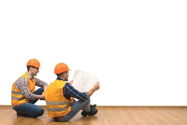 Два инженера с бумагой сидят на полу на фоне белой стены.