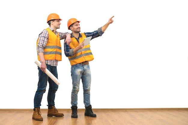 Два инженера с жестом планшета на белом фоне стены
