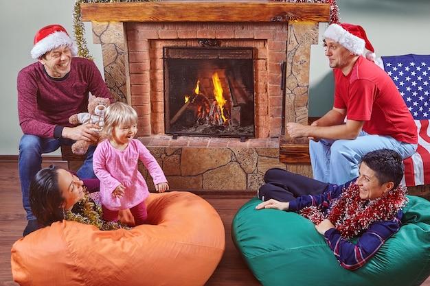 二人の家族は、クリスマスを祝うために暖炉の前のコテージで会いました。