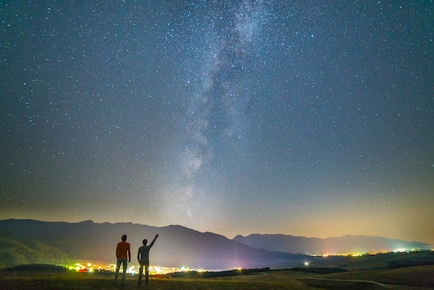 二人の友人は星の背景にジェスチャーを立てます。夜の時間