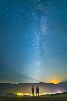 二人の友人は星空の背景に立っています。夜の時間