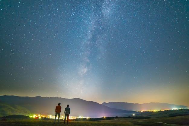 二人の友人は星の背景に立っています。夜の時間