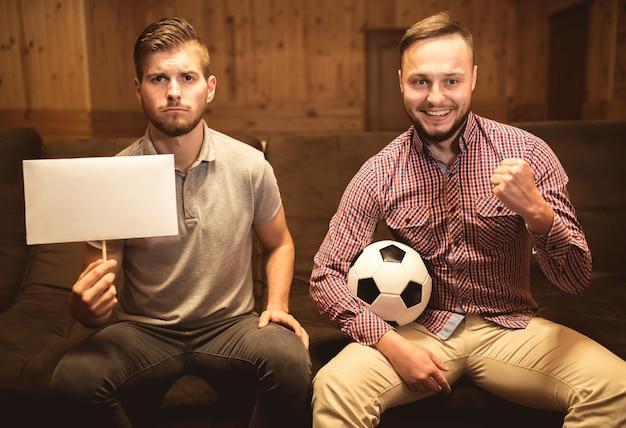 Два друга с мячом и пустой карточкой сидят на диване.