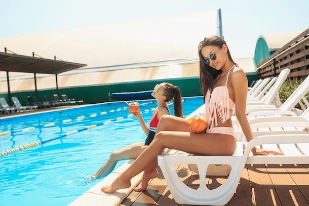 Две девушки играют и отдыхают в бассейне во время летних каникул