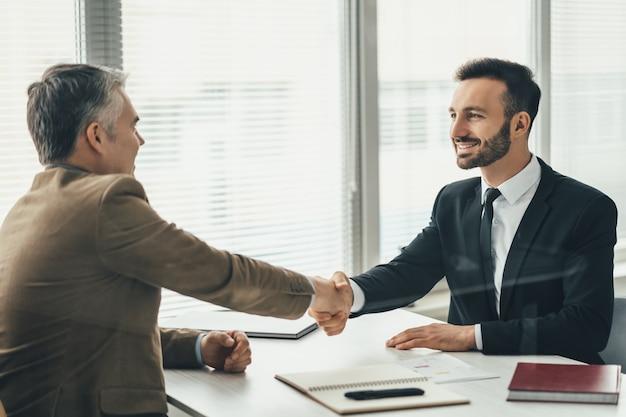 Два счастливых бизнесмена, обменивающихся рукопожатием над стаканом в офисе