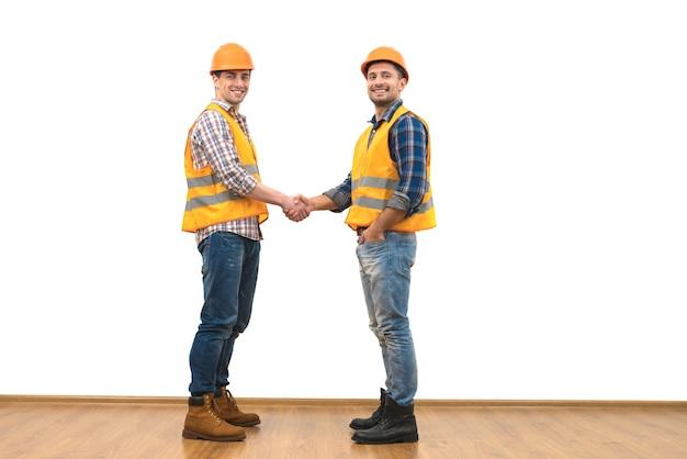 Рукопожатие двух счастливых инженеров на фоне белой стены