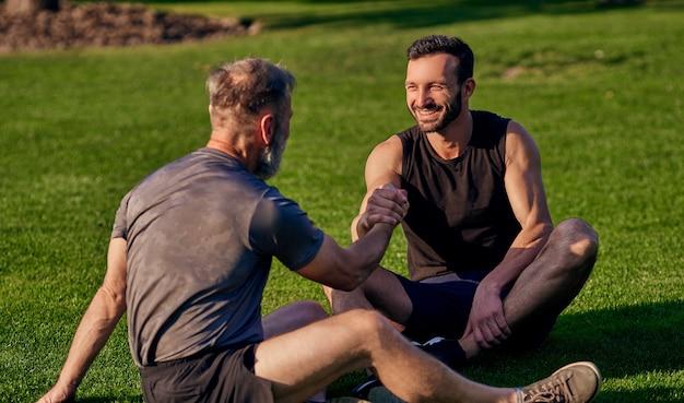 Два счастливых человека сидят на траве и пожимают друг другу руки