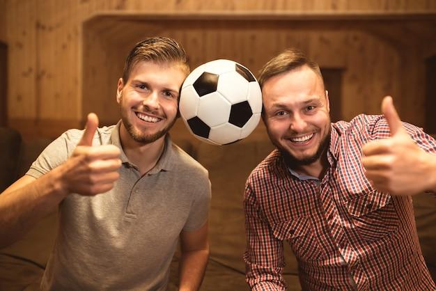 Два счастливых человека с большим пальцем руки вверх
