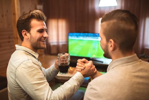 맥주를 마시는 행복한 두 남자가 축구를 보고 악수를 한다