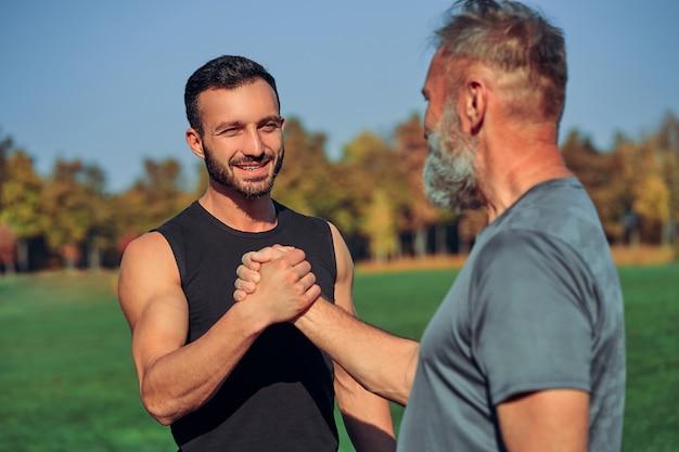 야외에서 인사하는 두 명의 행복한 스포츠맨