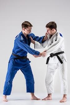 남자와 싸우는 두 judokas 전투기