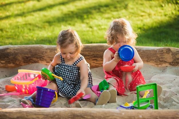 砂でおもちゃを遊んでいる二人の小さな女の赤ちゃん