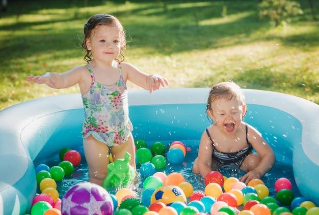 여름 화창한 날에 풍선 수영장에서 장난감을 가지고 노는 두 어린 아기 소녀