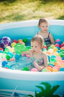 夏の晴れた日に膨脹可能なプールでおもちゃで遊ぶ2人の小さな女の赤ちゃん
