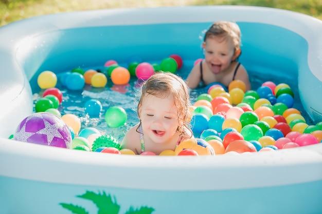 여름 화창한 날에 풍선 수영장에서 장난감을 가지고 노는 두 명의 작은 여자 아기