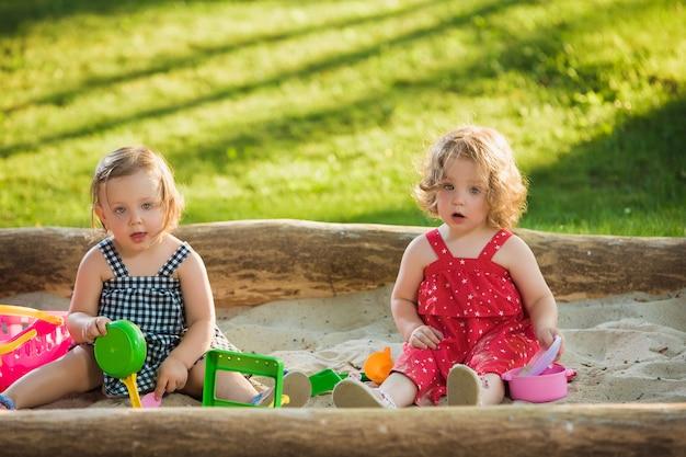Две маленькие девочки двухлетние играют в игрушки на песке на фоне зеленой травы