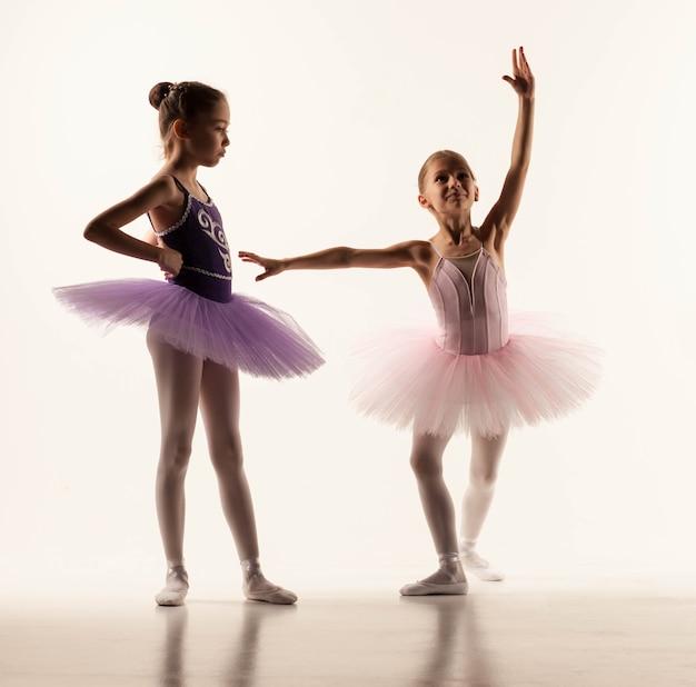 흰색 스튜디오에 서 있는 투투를 입은 두 명의 어린 발레 소녀