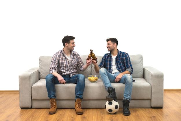 두 남자는 흰색 바탕에 소파에서 맥주를 마신다