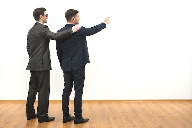 흰 벽 배경에 두 남자 제스처