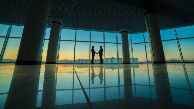 パノラマの窓の背景にオフィスで握手2人